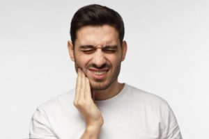 Man in white with tooth pain