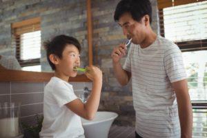 Man brushing his teeth looking in mirror