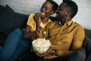 Couple eating popcorn on the couch together