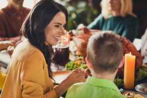 Woman and child at dinner table enjoying healthy thanksgiving