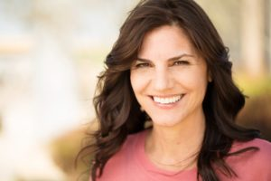 Woman smiling with healthy gums while sitting