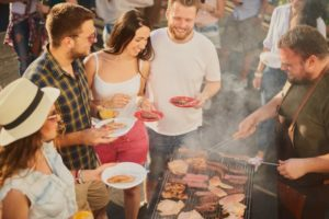 Group of friends with food surrounding a grill at summer BBQ