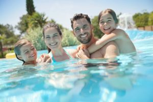 Family smiling in the pool together during a summer day